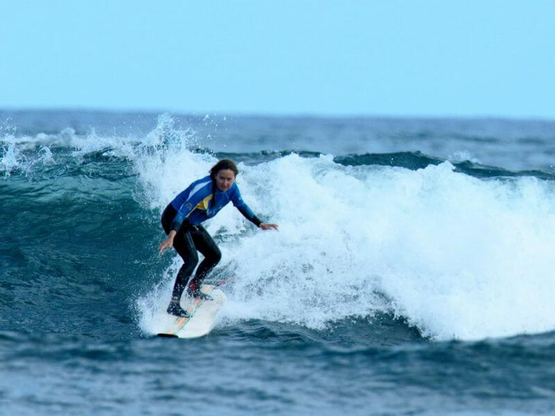 girl on the wave surfing in Fuerteventura Canary Islands